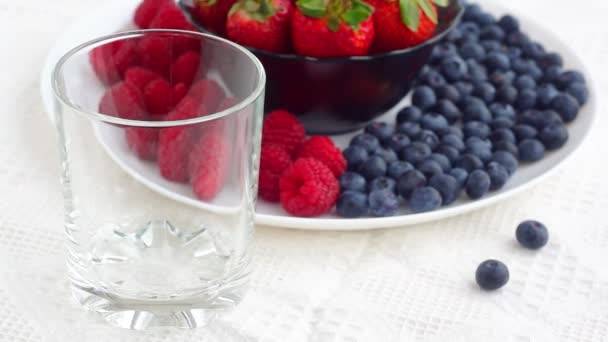 Natural milk pours in glass on berries background