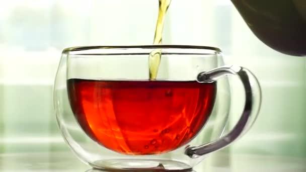Erős fekete tea öntenek a kannát forgó csésze