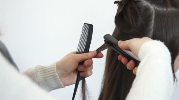 The hairdresser treats a strand of hair with a Curling iron