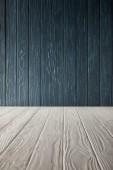 Fotografia tavolo in legno bianco e parete di legno blu scura