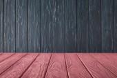 Fotografia Rosa a strisce da tavolo e scuri in legno parete blu