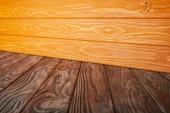 Fotografie hnědé pruhované podlah a oranžové dřevěné stěny