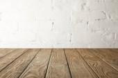 hnědá dřevěná stolní a bílá zeď s cihly