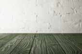 Photo dark green wooden tabletop and white wall with bricks