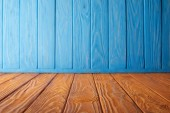 Photo brown striped tabletop and blue wooden wall