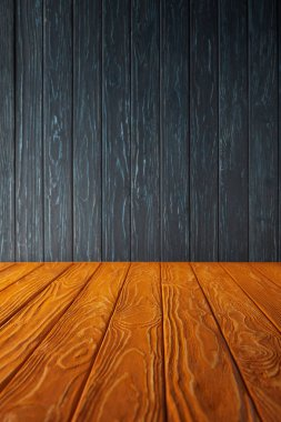orange wooden table and dark blue wooden wall