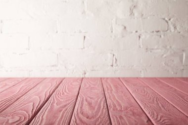 pink wooden tabletop and white wall with bricks