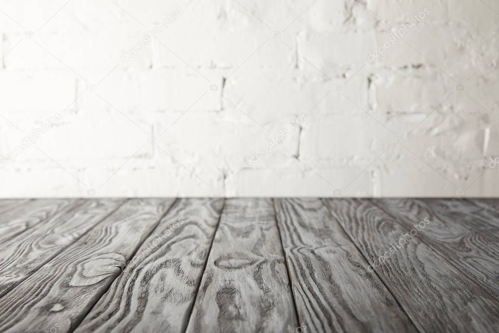grey wooden surface and white wall with bricks