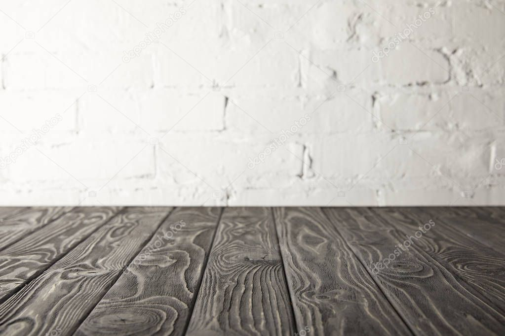 dark grey wooden tabletop and white wall with bricks