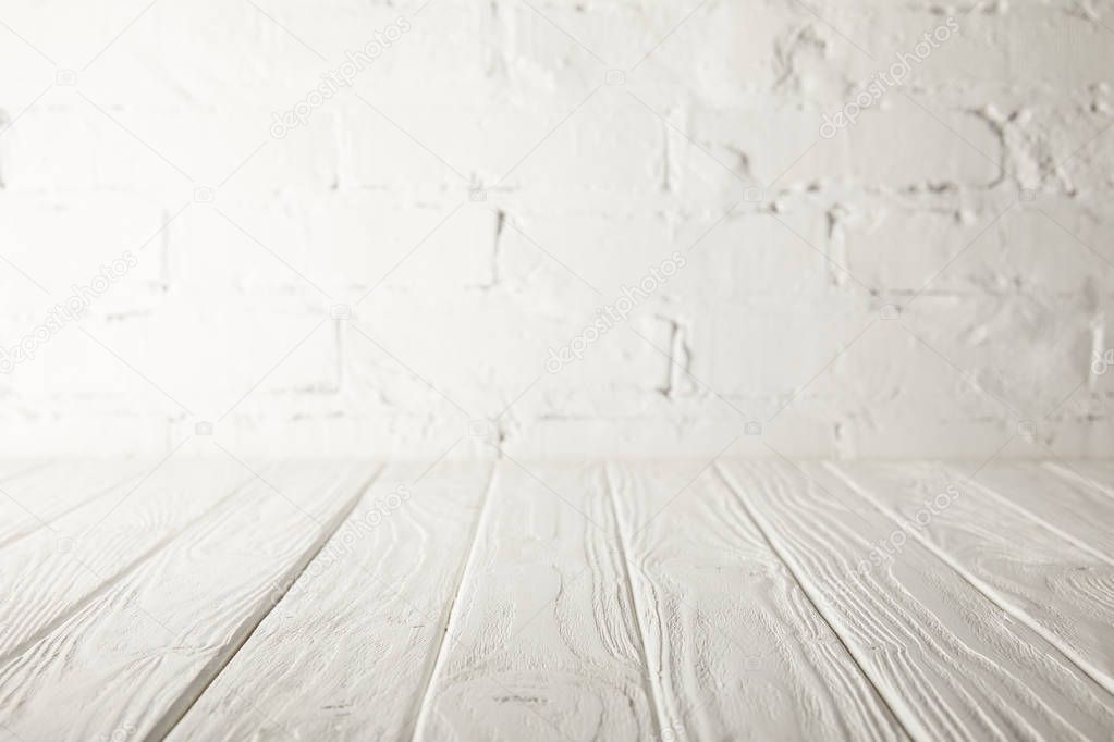 white wooden tabletop and white wall with bricks