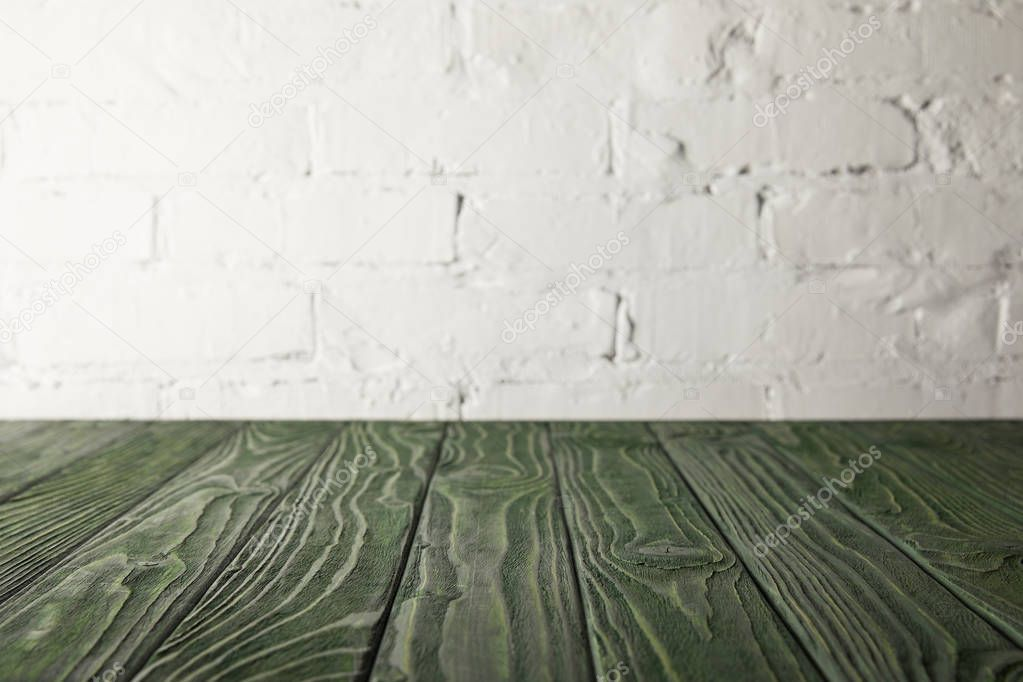 dark green wooden tabletop and white wall with bricks