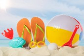 Fotografie Flip flops with beach ball and toys in sand on blue sky background