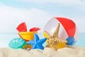 Strandröplabda- és játékszerek, homokban a kék ég háttér