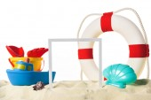 Fotografie Beach toys with life ring and frame in sand isolated on white