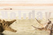 Fotografia Stelle marine con la conchiglia e iscrizione di vacanze sulla spiaggia di sabbia