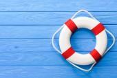 weißer und roter Rettungsring auf blauem Holzgrund