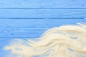 Sand waves on blue wooden background