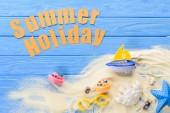 Plážové hračky od letní dovolené nápis na modré dřevěné pozadí