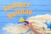 Női kéz, játék hajó, Nyári nyaralás felirat a kék fa háttér