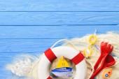 Život ring a hračka lodě na modré dřevěné pozadí