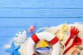 Rettungsring und Strandspielzeug auf blauem Holzhintergrund