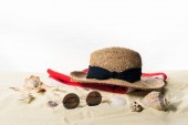 Straw hat and sunglasses with seashells in sand isolated on white