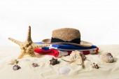Muscheln und Strohhut im Sand isoliert auf weiß