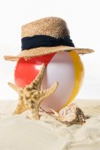 Beach ball under straw hat by seashell in sand isolated on white