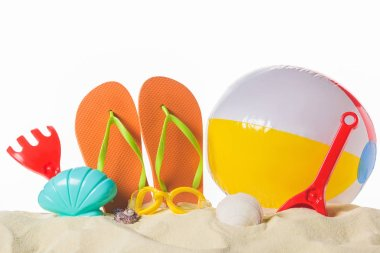 Beach ball and flip flops in sand isolated on white