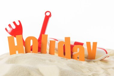 Beach toys and word Holiday in sand isolated on white