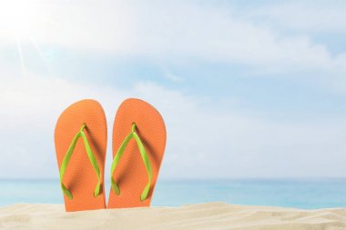 Pair of flip flops in sand on blue sky background