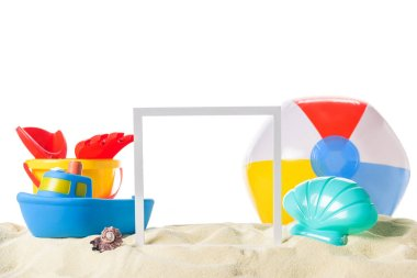 Beach toys and frame in sand isolated on white