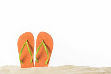 Pair of flip flops in sand isolated on white
