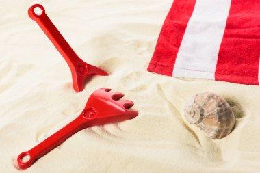 Towel with toys and seashell on sandy beach stock vector