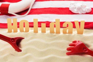 Beach toys and towel with Holiday inscription on sandy beach