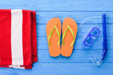 Flip flops with mask and towel on blue wooden background