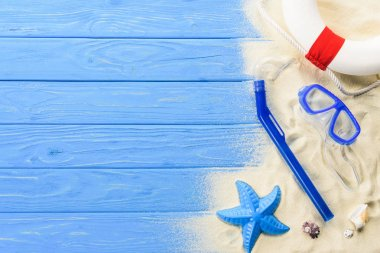 Beach toys and diving mask on blue wooden background