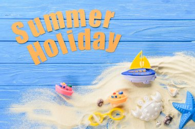 Beach toys by Summer holiday inscription on blue wooden background stock vector