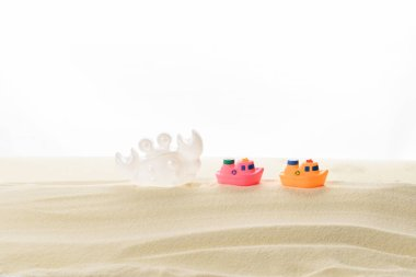 Toy boats and crab in sand isolated on white stock vector