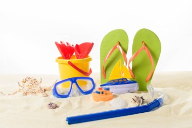 Beach toys and flip flops with diving mask in sand isolated on white