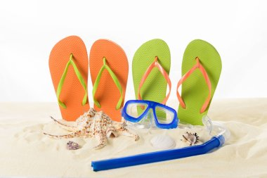 Flip flops and diving mask in sand isolated on white
