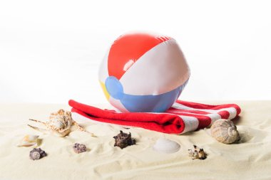 Beach ball on towel by seashells in sand isolated on white