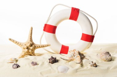 Life ring and seashells in sand isolated on white