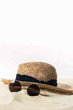 Straw hat and sunglasses in sand isolated on white stock vector