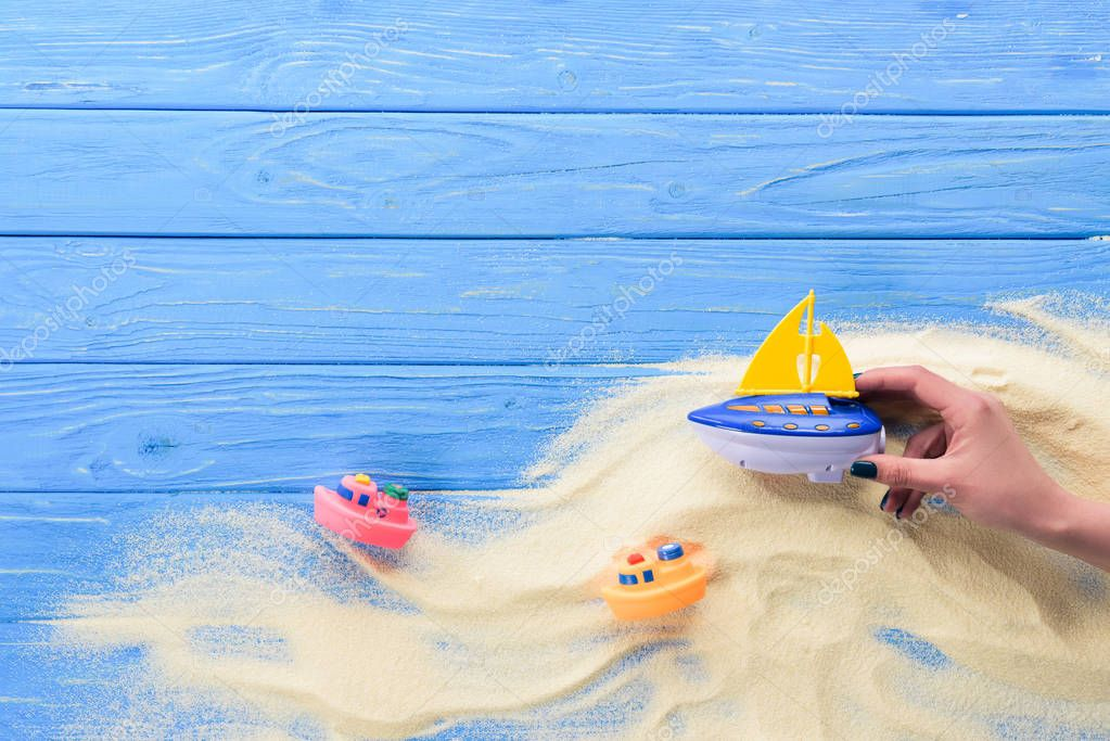 Woman playing with toy boat on blue wooden background