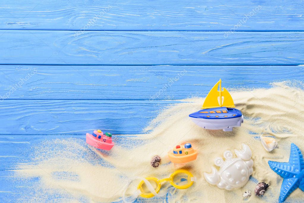 Beach toys in sand on blue wooden background