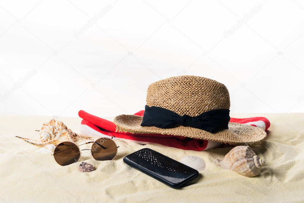 Straw hat on towel and sunglasses with seashells in sand isolated on white