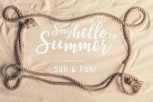 Photo Frame of ship rope on sandy beach with say hello to summer lettering