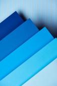 Fotografie Papierbögen in Blautönen auf gestreiften Hintergrund