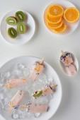Fotografie Draufsicht der köstlichen hausgemachten Eis am Stiel mit Eiswürfeln und in Scheiben geschnittenen Kiwi und Orange auf grau